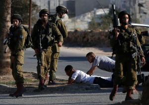 Israeli soldiers detain Palestinians during clashes at a protest  against Israeli military action in Gaza, in Silwad near Ramallah
