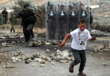 A young Palestinian protester runs away