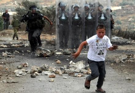 A young Palestinian protester runs away