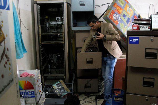 journalist-inspects-damage-to-Al-Khalil-radio-after-Israeli-raid-November-21-2015